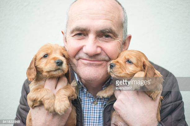 Smiling handsome man with cocker spaniel puppies