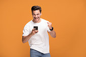 Handsome smiling excited man holding mobile phone posing on yellow studio background.