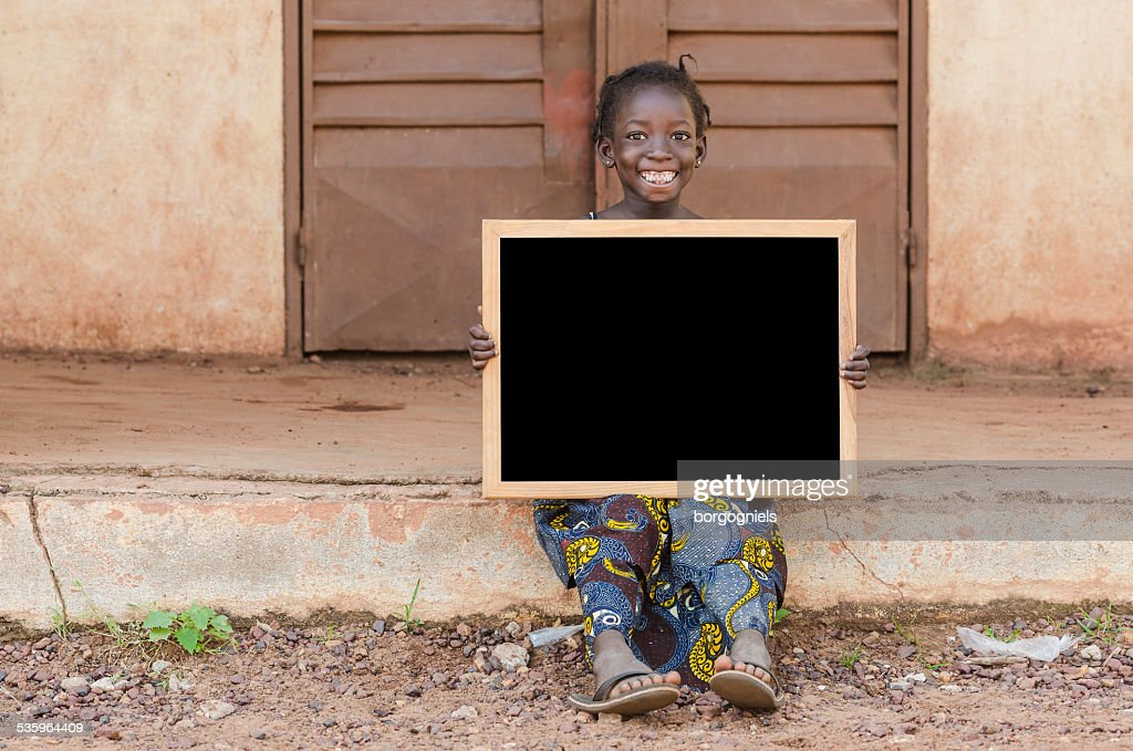 Smiling Happy African Schoolgirl Holding Blackboard Sitting in School : Stock Photo