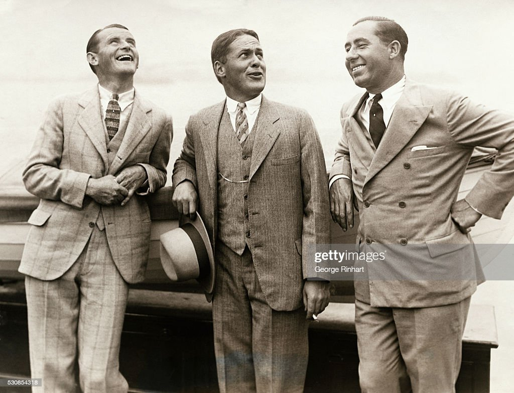 Smiling, happy and the proud possessor of the British Open Golf title. Bobby Jones of Atlanta, Georgia, arrived in New York, on the S.S. Aquitania of the Cunard Line. He ws greeted by a delegation of Atlantans and the major portion of the populace of lower New York, besides being accorded an official welcome. Photo shows on the S.S. Aquitania, a trio of 'Ace High Golfers,' on the deck of the ship; Left to right: Al Watrous, Bobby Jones, the champion, and Walter Hagen.