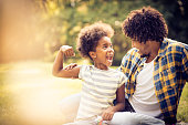 African American father and daughter playing in nature.