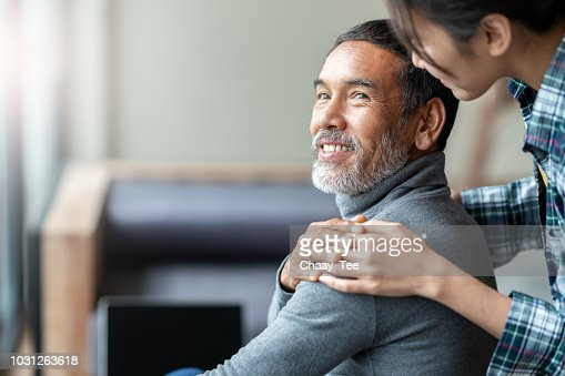 Smiling happy older asian father with stylish short beard touching daughter's hand on shoulder looking and talking together with love and care. Family relationship with bond and care concept. : Foto de stock