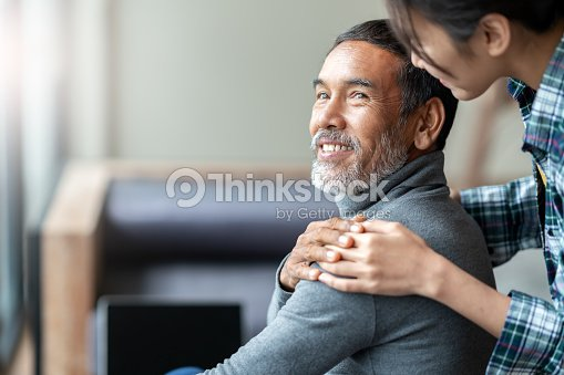 Smiling happy older asian father with stylish short beard touching daughter's hand on shoulder looking and talking together with love and care. Family relationship with bond and care concept. : Stock Photo