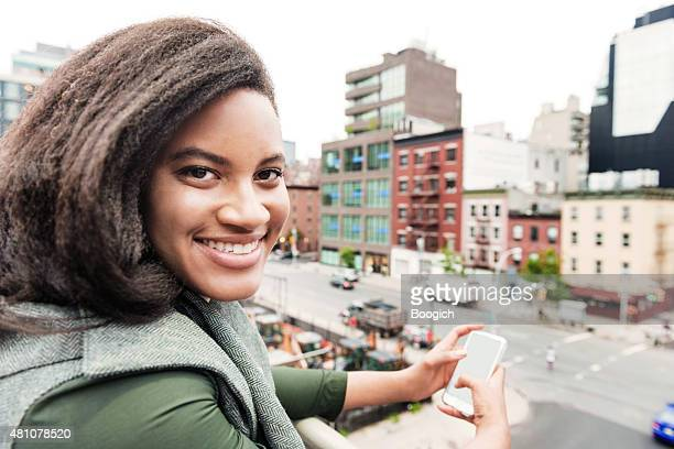 Smiling Happy Urban NYC Woman with Phone Above City Buildings