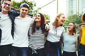 Smiling happy young adult friends arms around shoulder outdoors friendship and connection concept