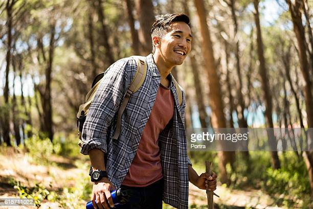 Smiling hiker holding stick and water bottle