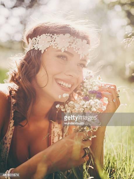 Smiling hippie girl lying in grass holding wild flowers