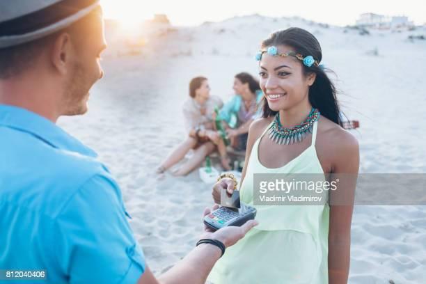 Sonriente mujer hippie con tarjeta de crédito en la playa