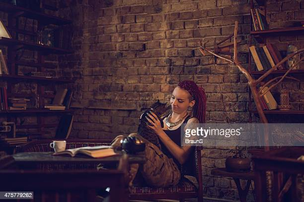 Smiling hipster woman enjoying with her cat at home.