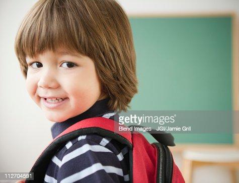 Smiling Hispanic boy wearing backpack