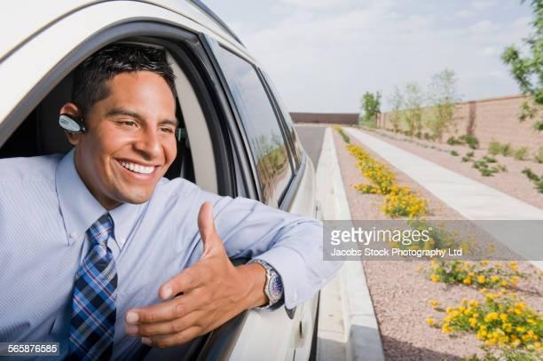 Smiling Hispanic businessman driving car