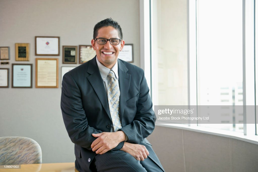 Smiling Hispanic businessman sitting on desk