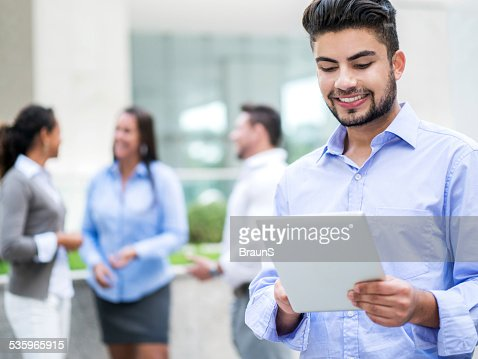Smiling Hispanic businessman using touchpad. : Stock Photo