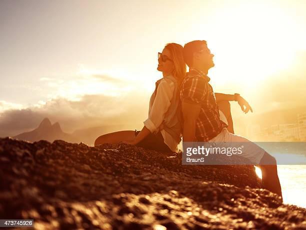 Smiling Hispanic couple sitting back to back on a rock.