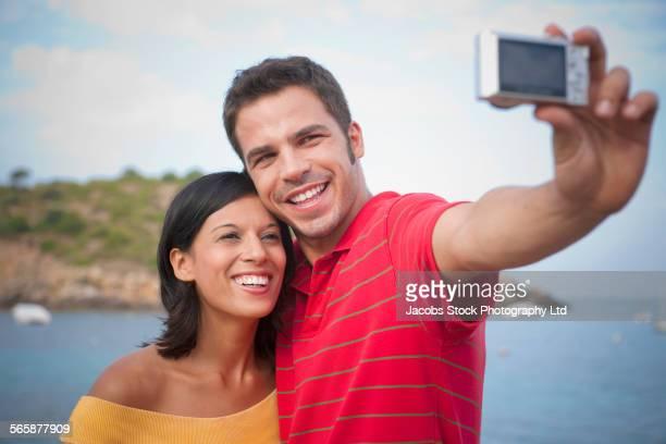 Smiling Hispanic couple taking selfie near harbor