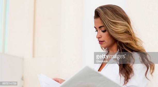 Smiling Hispanic doctor reading folder