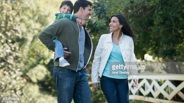 Smiling Hispanic family walking in park