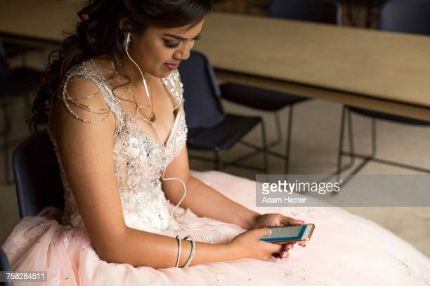 Smiling Hispanic girl listening to cell phone with earbuds