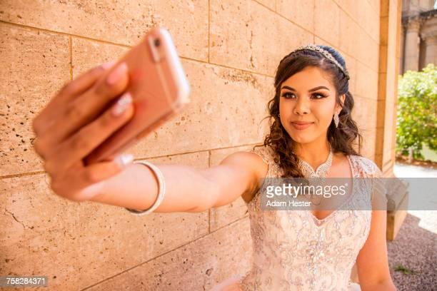 Smiling Hispanic girl posing for cell phone selfie