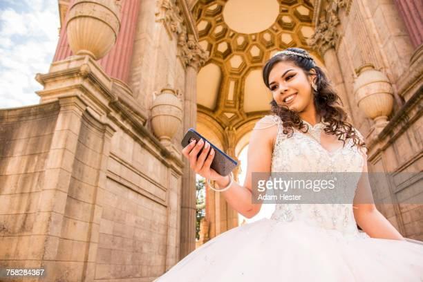 Smiling Hispanic girl texting on cell phone