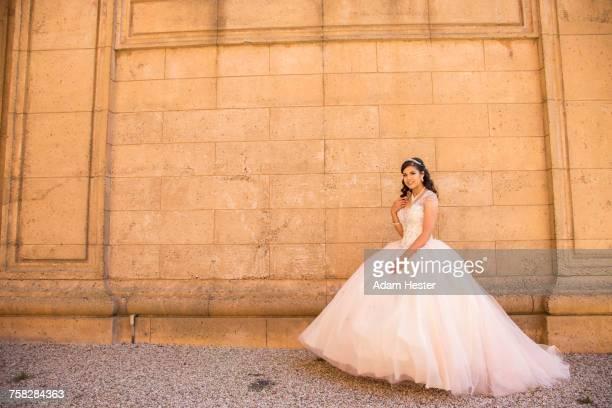 Smiling Hispanic girl wearing gown near wall