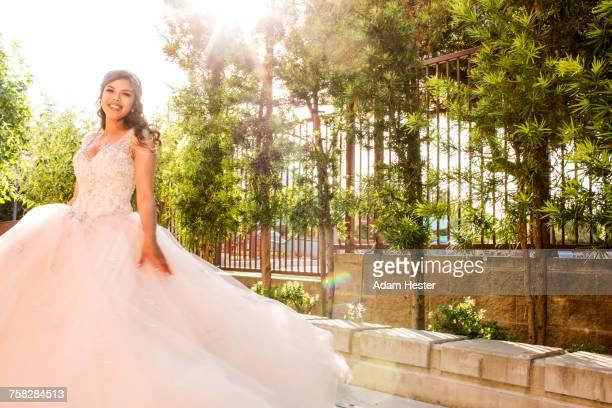 Smiling Hispanic girls wearing gown in park