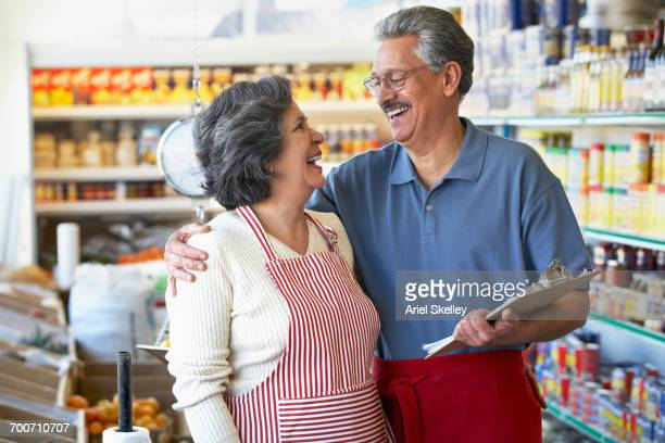 Smiling Hispanic grocery store owners hugging