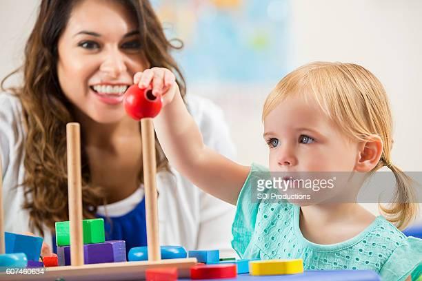 Smiling Hispanic teacher working with cute preschooler