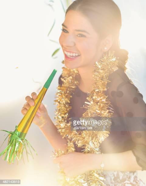 Smiling Hispanic woman celebrating New year's Eve