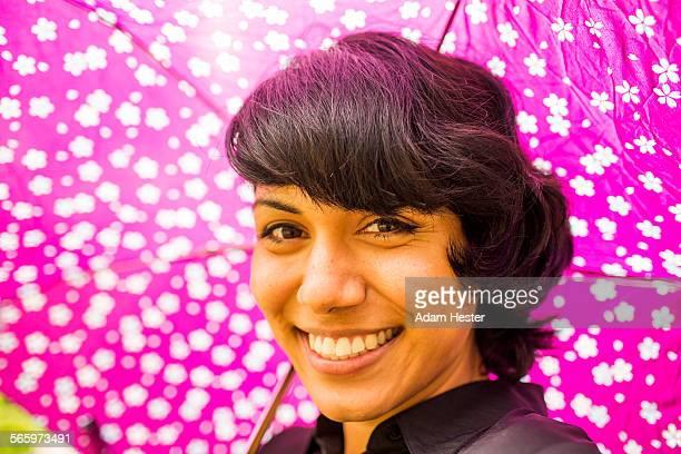 Smiling Hispanic woman holding pink umbrella