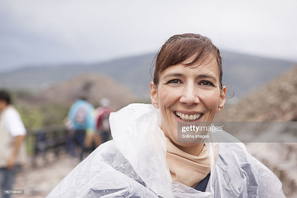 Smiling Hispanic woman in rain coat : Stock Photo