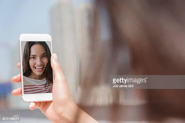 Smiling Hispanic woman posing for cell phone selfie