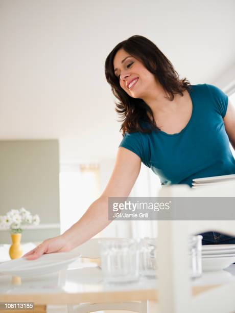 Smiling Hispanic woman setting dining table