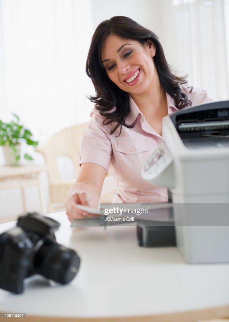 Smiling Hispanic woman using printer
