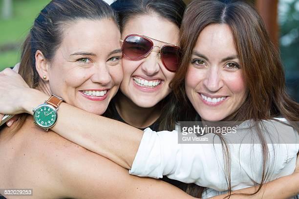 Smiling Hispanic women hugging outdoors