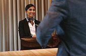 Smiling hotel receptionist talking with male guest at reception counter. Happy female receptionist worker standing at hotel counter with businessman checking in.