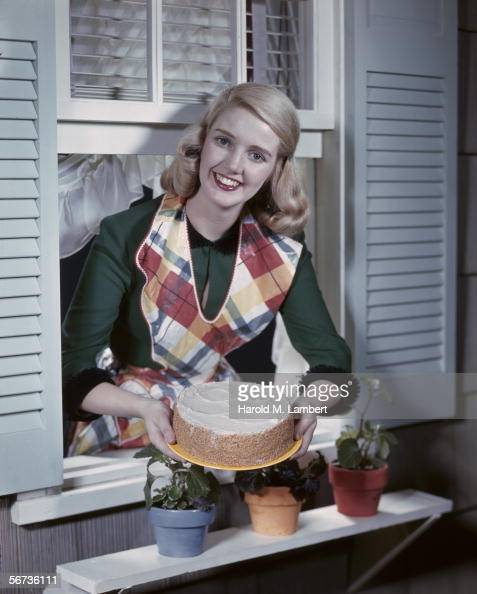 A smiling housewife leans out of a window with a freshly baked cake early 1950s