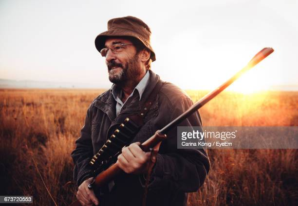 Smiling Hunter With Shotgun Standing In Field During Sunrise