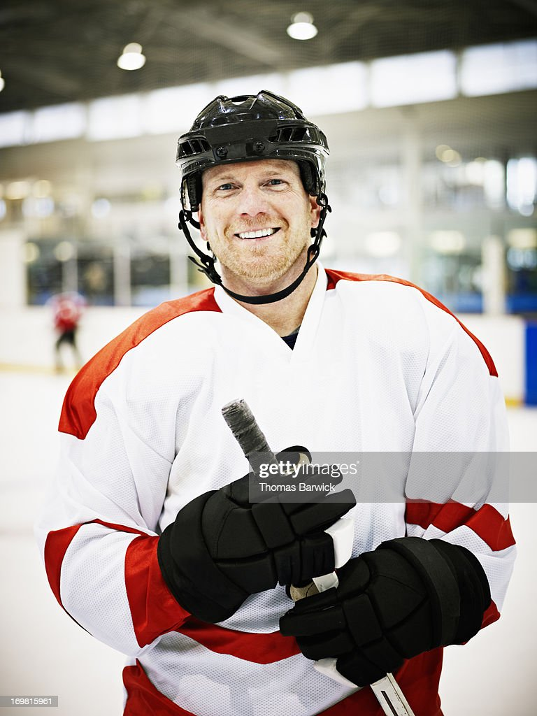 Smiling ice hockey player standing on ice : Stock Photo
