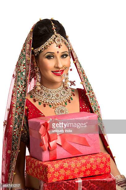 Smiling Indian bride in traditional wedding dress holding gifts