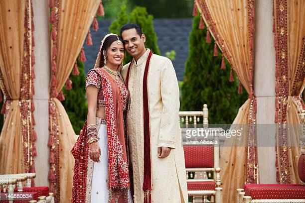 Smiling Indian couple in traditional wedding clothing
