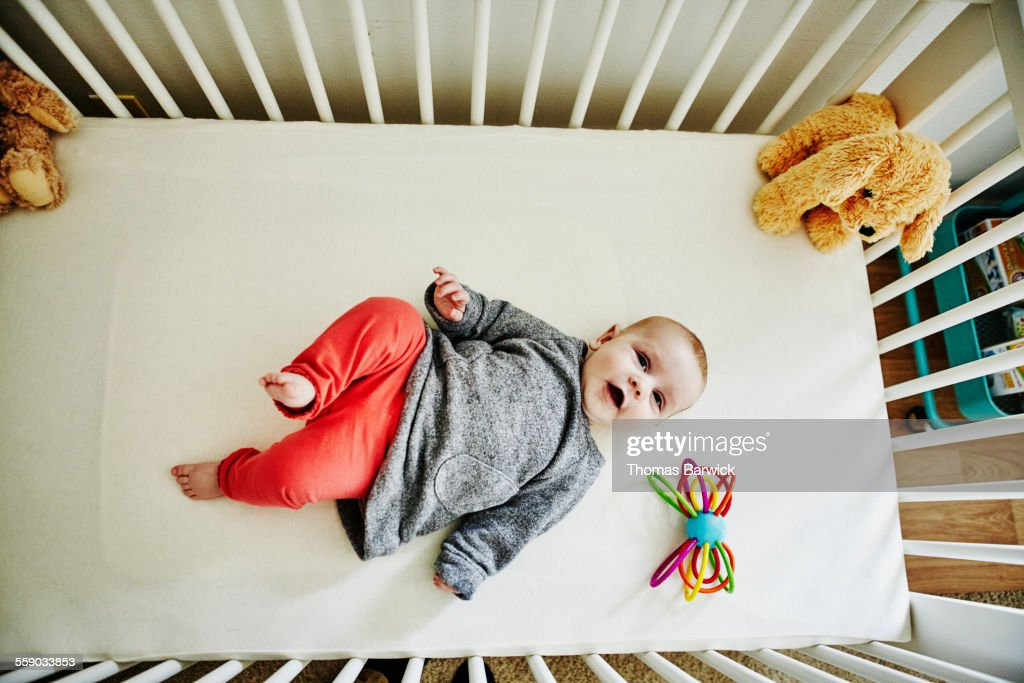 Smiling infant girl lying in crib with toys
