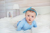 Smiling infant in blue clothes crawls on a bed in bedroom