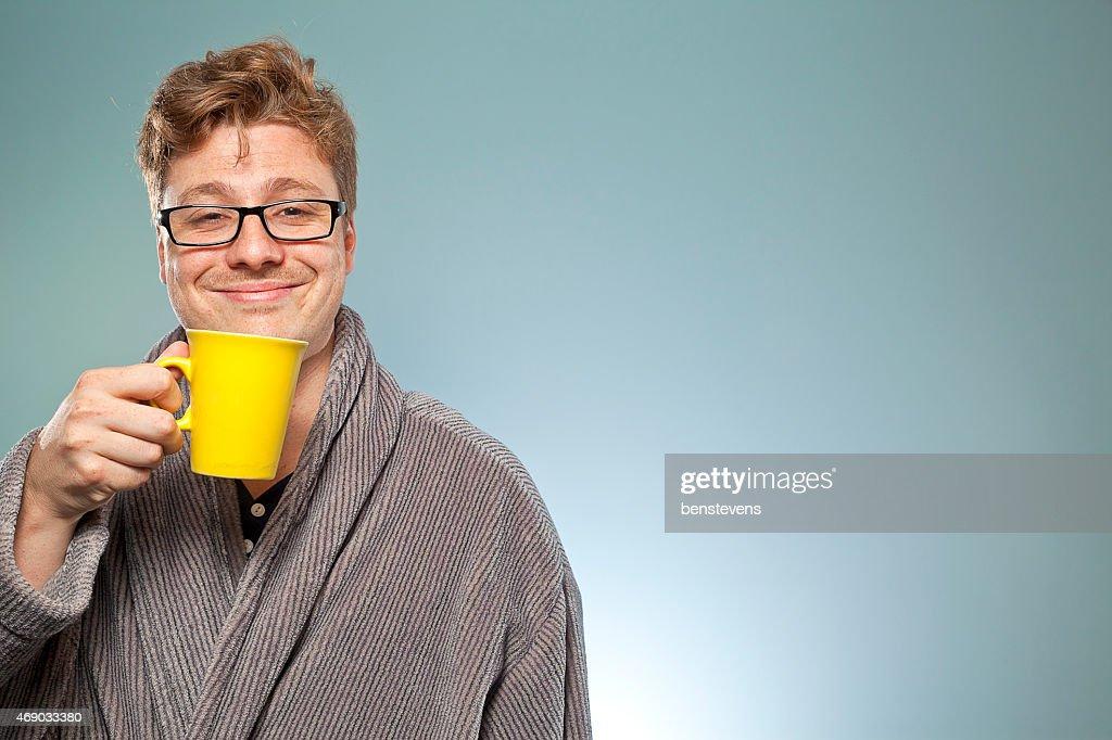 Smiling intelligent looking mature man drinks coffee