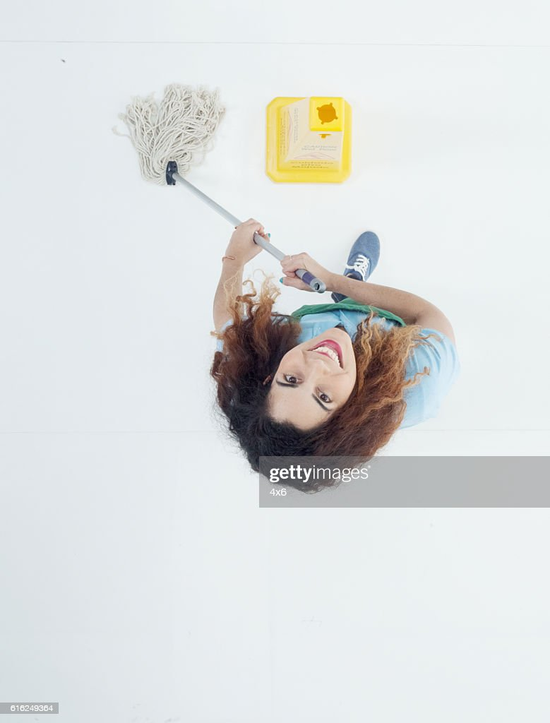 Smiling janitor cleaning and looking up : Stock Photo