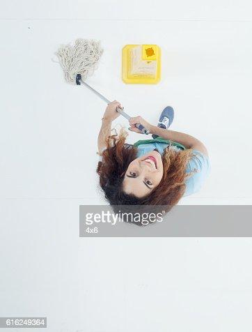 Sorridente empregado de limpeza limpeza e olhando para cima : Foto de stock