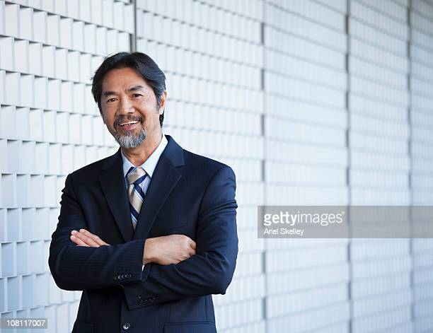 Smiling Japanese businessman with arms crossed