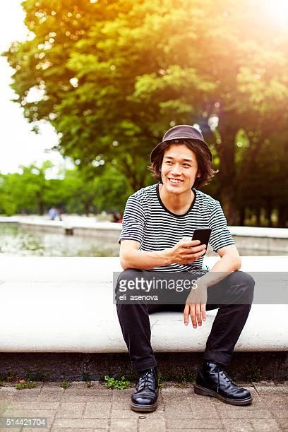 笑顔のティーンに、スマートフォンでパーク、東京。