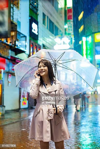 Lächelnd Japanische Frau mit Regenschirm am Telefon in Tokio