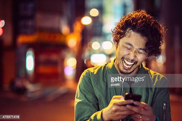 笑顔の若い男性、スマートフォンで都会の風景